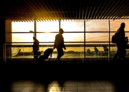 This photo is of a traveler at an airport with a suitcase to accompany the story on bleisure travel.